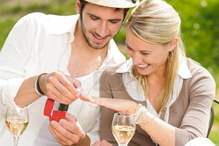 Photo pour Jeune homme proposant à petite amie offrant bague de fiançailles terrasse ensoleillée - image libre de droit