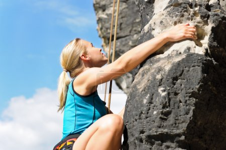 Photo for Rock climbing blond woman on rope sunny day - Royalty Free Image