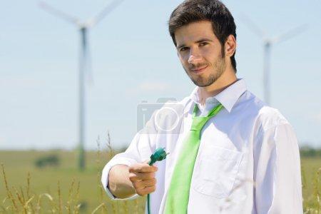 Photo pour Énergie verte - jeune entrepreneur tenir prise dans domaine avec moulin à vent - image libre de droit