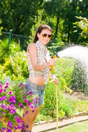Summer garden smiling woman watering hose garden flower
