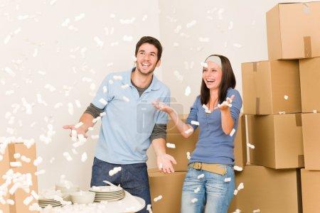 Foto de Mudanza casa joven pareja alegre avientan poliestireno maní desempacando cajas - Imagen libre de derechos