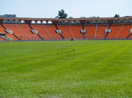 Photo for Empty green football field with seats at stadium - Royalty Free Image