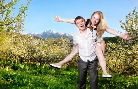 Couple having fun around bloomy trees