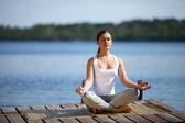 Girl trains yoga on the pier near lake