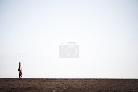 Photo pour Femme marchant sur le sable noir - image libre de droit