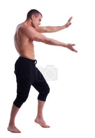 Athletic man posing nude push forward
