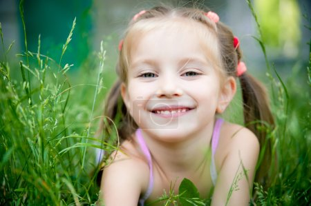 Photo for Cute little girl smiling in a park close-up - Royalty Free Image
