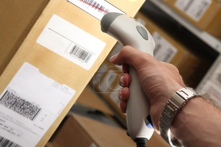 Photo for A man gets on the barcode scanner in operations directed on printed barcode. Warehouse scene. - Royalty Free Image