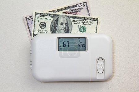 Photo for In door heating thermostat set at a room temperature and money - Royalty Free Image