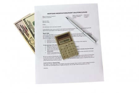 Mortgage modification form with calculator and pen...