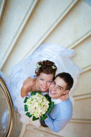 Photo pour Heureux marié et mariée est debout dans les escaliers - image libre de droit