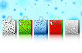 A collection of 5 different colored holly and berry designed holiday gift bags against a winter snowflake background