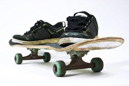 Photo pour Une planche de skate et des chaussures trouées sur un fond blanc représentant les sports de glisse - image libre de droit