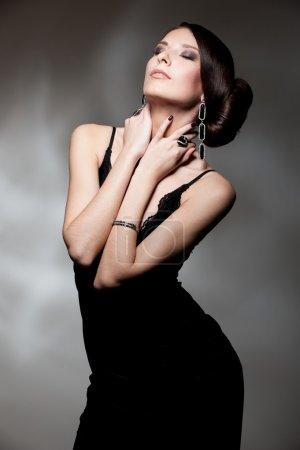 Photo pour Affriolante femme en robe noire posant sur fond foncé - image libre de droit