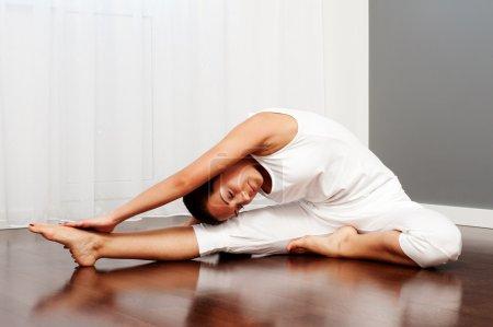 Photo pour Jeune femme faisant de l'exercice d'étirement sur le sol - image libre de droit