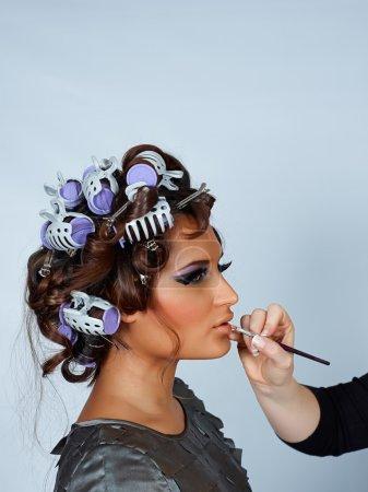 Photo pour Belle jeune modèle latino avec ses cheveux en bigoudis et maquillage fait avant le tournage de mode, avec de l'espace pour le texte - image libre de droit