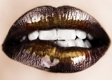 Photo pour Femme mordant ses lèvres avec du rouge à lèvres noir brillant et de la poudre dorée brillance  . - image libre de droit