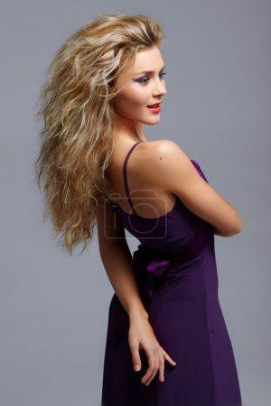 Photo pour Femme blonde avec des lèvres rouges et maquillage yeux de chat en robe violette. sous la direction de raw dans prophoto RVB 16 bits. - image libre de droit