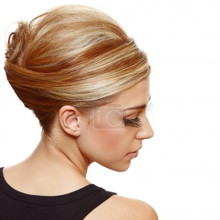 Photo pour Belle femme blonde avec de faux cils longs portant des cheveux dans un style français classique roll updo - image libre de droit