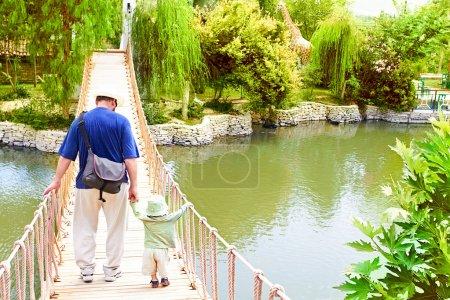 Photo pour Jeune père tenant la main avec un petit enfant en bas âge alors qu'il lui apprend à équilibrer et marcher sur le pont au-dessus du lac dans le parc en Turquie - image libre de droit