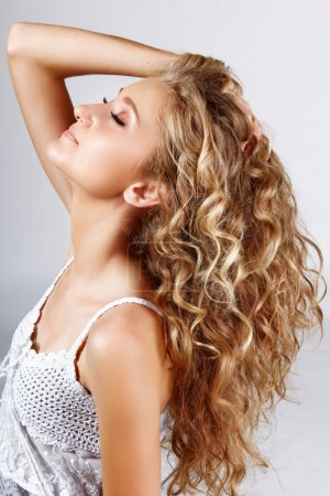 Photo for Beautiful strawberry blond teenage girl with long curly hair over grey studio background . - Royalty Free Image