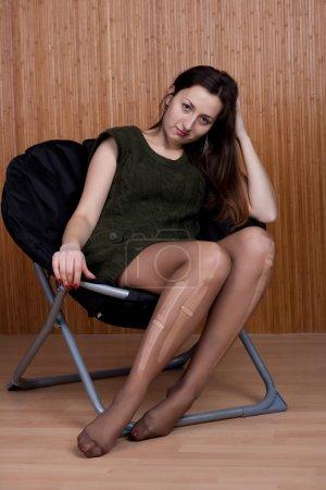 Sad pensive girl in torn tights