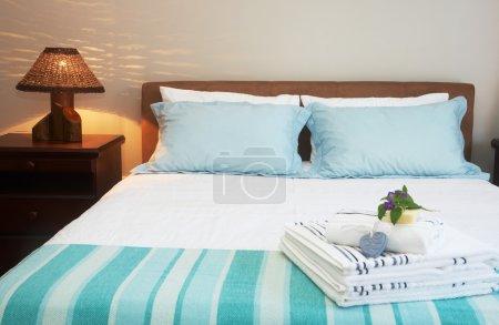Photo pour Belle chambre intérieure avec draps blancs et serviettes rayées - image libre de droit