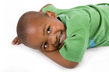 Photo for Adorable 3 year old black or African American boy with a smile lying on the floor looking at you - Royalty Free Image