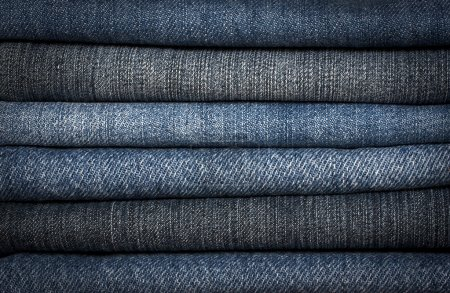 A pile of different types of blue denim jeans closeup