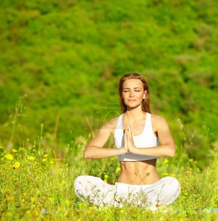 Photo pour Femelle en bonne santé, faire du yoga en plein air, assis en posture de lotus, soins du corps & concept de paix intérieure - image libre de droit