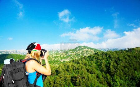 Photo for Tourist girl taking pictures of a high green mountains landscape, tourism travel vacation fun concept - Royalty Free Image