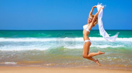 Photo for Jumping happy girl on the beach, fit sporty healthy sexy body in bikini, woman enjoys wind, freedom, vacation, summertime fun concept - Royalty Free Image