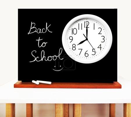Photo pour Concept de retour à l'école, écriture sur un tableau noir avec grande horloge blanche - image libre de droit