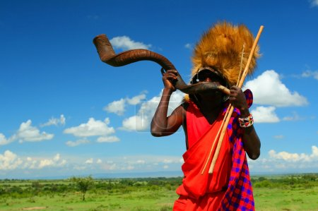 Masai warrior playing traditional horn. Africa. Ke...