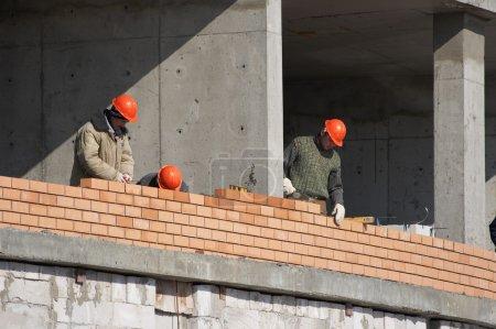 Photo pour Constructeurs, casque, briques, pose de bâtiments, monolithe , - image libre de droit