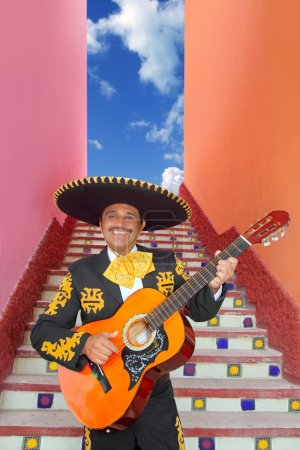Photo for Charro Mariachi singer playing guitar in Mexico stairway - Royalty Free Image