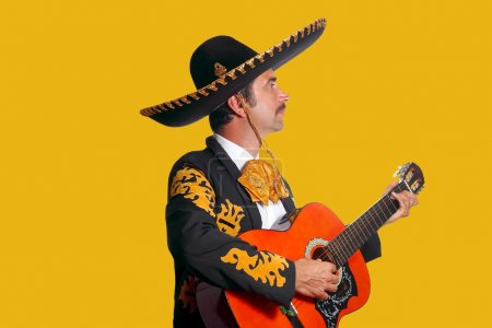 Photo for Charro Mariachi playing guitar on yellow background - Royalty Free Image