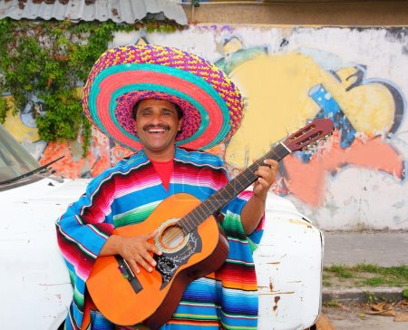 Photo for Mexican humor man smiling playing guitar sombrero poncho in street - Royalty Free Image