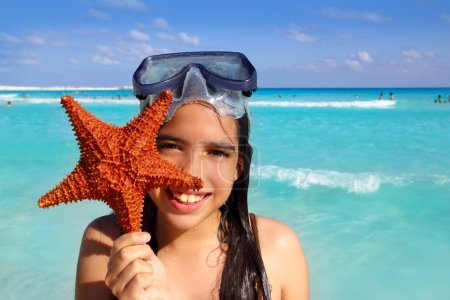 Photo for Latin tourist girl holding starfish in tropical beach - Royalty Free Image