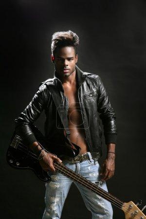 Photo pour Musicien star afro américain de rock avec guitare basse et veste de cuir - image libre de droit