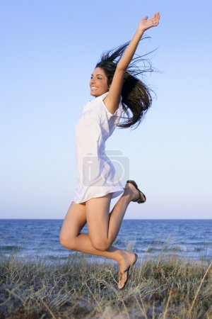 Photo for Beautiful brunette jumping in the summer blue beach - Royalty Free Image