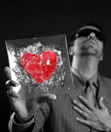 Broken red glass heart businessman metaphor