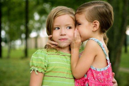 Photo pour Deux jumelles filles jumelles chuchotent à l'oreille, en plein air sur le parc vert - image libre de droit