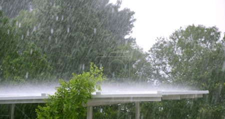 Raining over a white roof in a hurricane storm