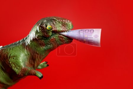 Toy dinosaur with euro note in its yaws