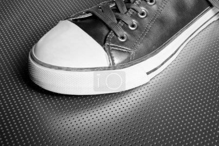 Silver sport shoe detail over gray steel