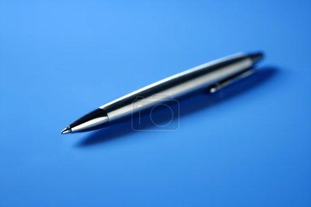 Photo pour Stylo à rouleau simple en acier gros plan sur fond bleu - image libre de droit