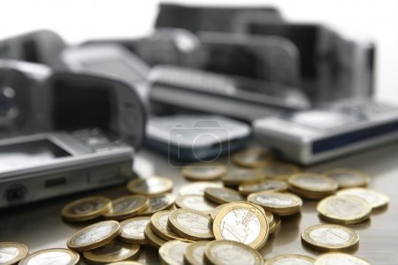 Assorted mixed mobile phones with lots of euro coin