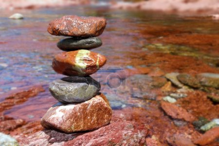 Rolling stones stacked red rodeno limestone in river