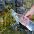 Source of spring water bottle filling holding hand...